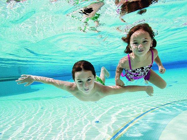 kinderen in zwembad, huis met zwembad
